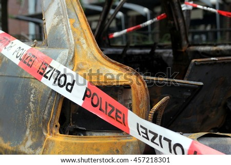 Close-up of a burned out vehicle with police barrier tape