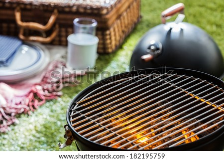 Close up of a burning hot fire in a portable barbecue with an empty grill and a wicker picnic hamper visible on a green lawn behind - stock photo