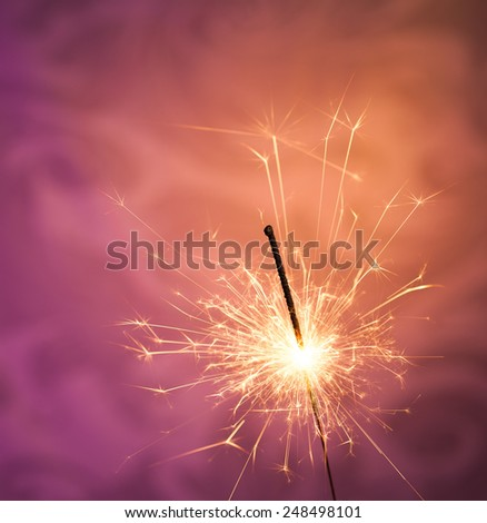 Close up of a burning sparkler on a purple and gold background - stock photo