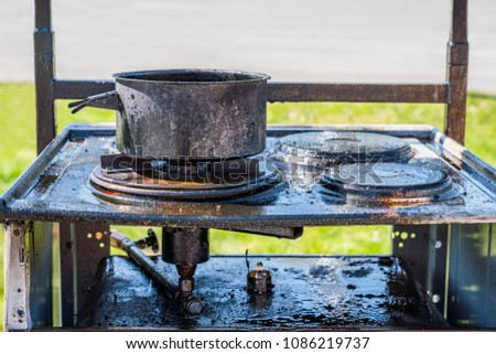 Close up of a burnt black gas stove covered with grease, a burnt pot on top.