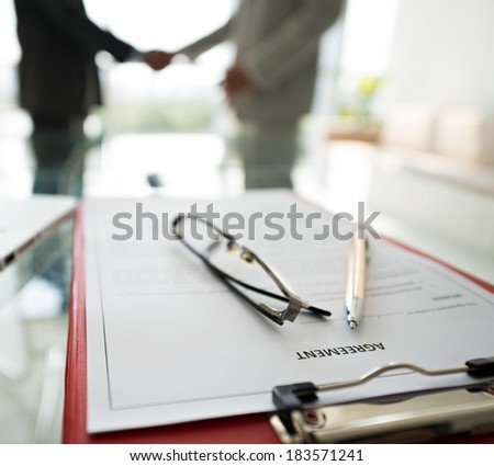 Close-up of a business agreement document on the foreground, partners handshaking on the background  - stock photo