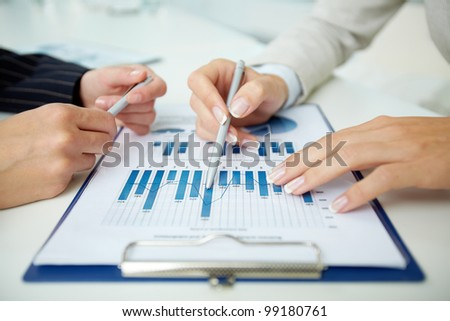 Close-up of a business document and business people discussing it