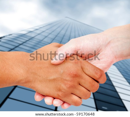 Close up of a business handshake with an office building behind