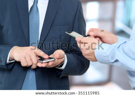 Close up of a business men using mobile smart phones - stock photo