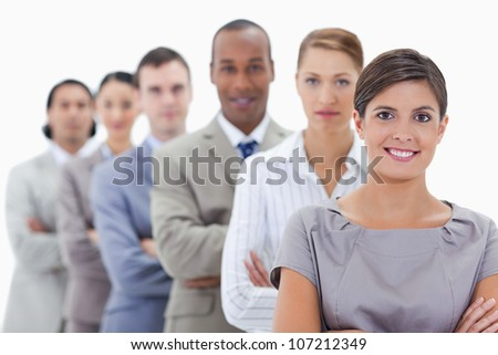 Close-up of a business team in a single line crossing their arms with focus on the first woman - stock photo