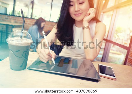 close up of a business woman analyzing business graphs on digital tablet - stock photo