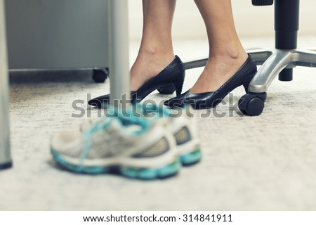 Close up of a business woman sports shoes in an office - stock photo