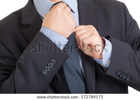 Close-up of a businessman adjusting his tie - stock photo