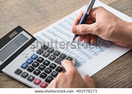 Close-up Of A Businessman Analyzing Accounting Document With Calculator At Desk In Office - stock photo