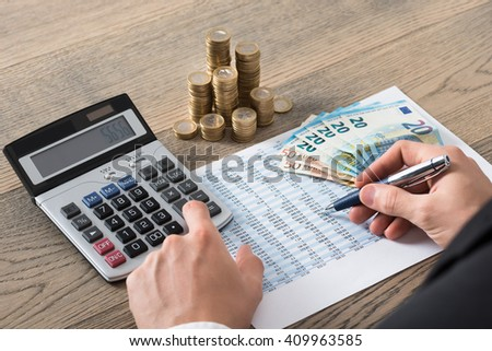 Close-up Of A Businessman Analyzing Financial Report Witch Stack Of Coins - stock photo