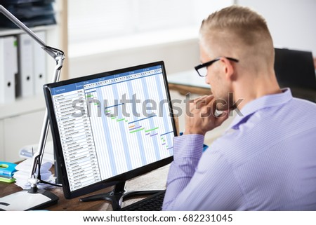 Close-up Of A Businessman Analyzing Gantt Chart On Computer Over The Wooden Desk