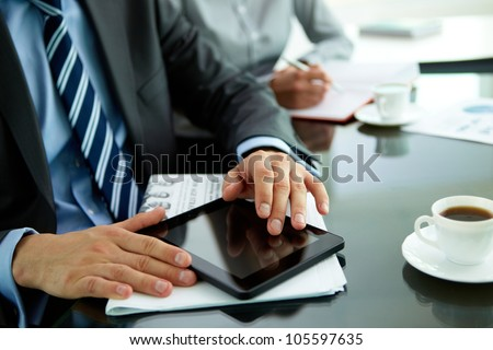 Close-up of a businessman at his workplace with a newspaper, cup of coffee and a tablet computer - stock photo
