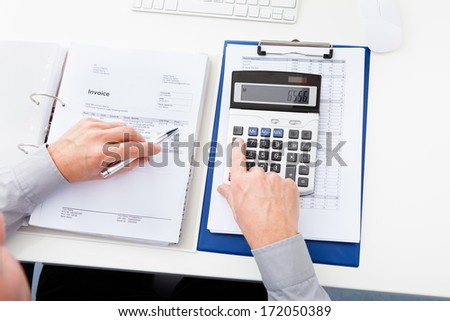 Close-up Of A Businessman Calculating Finance At Desk - stock photo