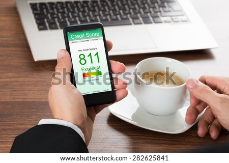 Close-up Of A Businessman Checking Credit Score Online On Cellphone While Having Coffee - stock photo