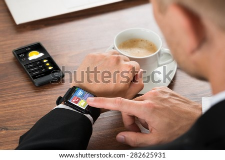 Close-up Of A Businessman Checking Weather On Smartwatch - stock photo