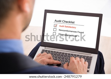 Close-up Of A Businessman Filling Audit Checklist Form On Laptop - stock photo