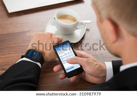 Close-up Of A Businessman Filling Survey Form On Cellphone - stock photo