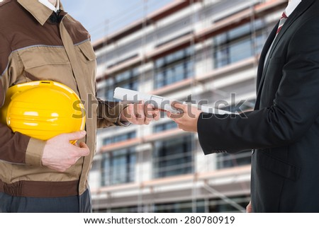 Close-up Of A Businessman Giving Blueprint To Architect - stock photo