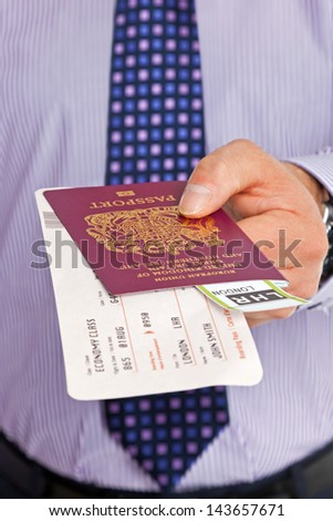 Close-up of a businessman handing over his boarding pass and passport at airport check-in. The tickets are mock ups and all details and names are generic.