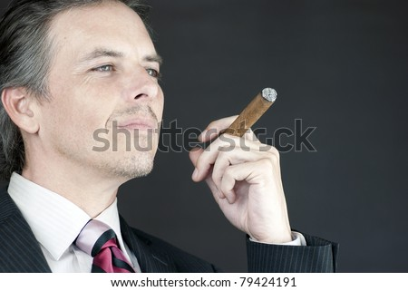 Close-up of a businessman holding a cigar in contemplation. - stock photo