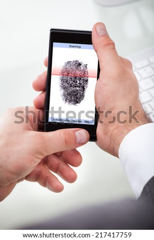 Close-up Of A Businessman Holding Cellphone Scanning Finger - stock photo