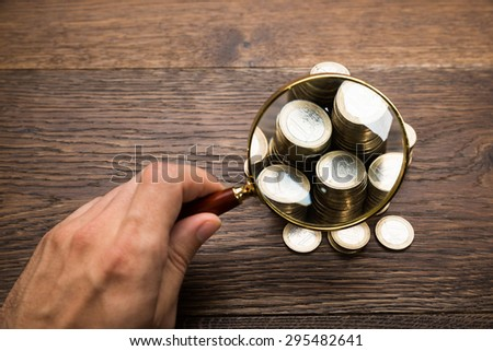 Close-up Of A Businessman Holding Magnifying Glass Over Coins On Desk - stock photo