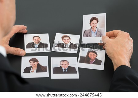 Close-up Of A Businessman Holding Photograph Of A Female Candidate - stock photo