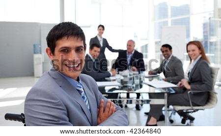Close-up of a businessman in a wheelchair with his colleagues in the background - stock photo