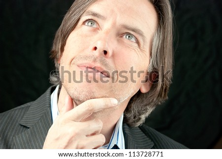 Close-up of a businessman looking up while pondering. - stock photo
