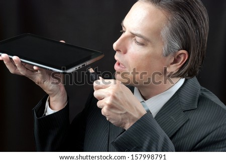 Close-up of a businessman plugging a usb cable into his tablet - stock photo