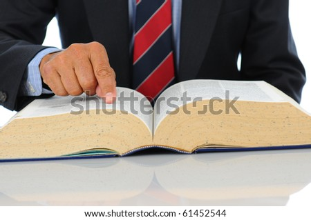 Close up of a businessman pointing to a line in a large book. Horizontal format showing hand, book and torso only with shallow depth of field, focus on the hand.