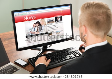 Close-up Of A Businessman Reading News On Computer At Office - stock photo