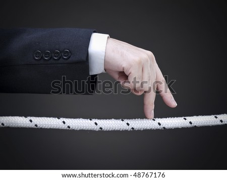 Close up of a businessman's fingers walking on the tightrope. Conceptual image.