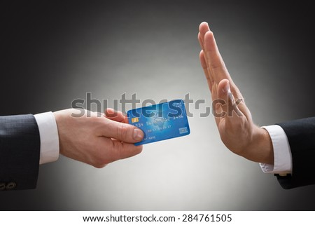 Close-up Of A Businessman's Hand Avoiding Credit Card - stock photo