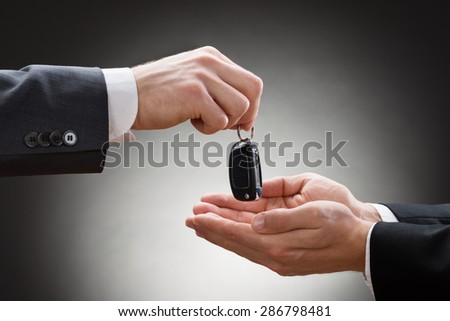 Close-up Of A Businessman's Hand Handing Car Key To Another Person - stock photo