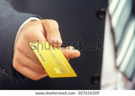 Close up of a businessman`s hand,holding gold credit card. - stock photo