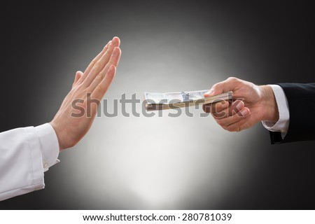 Close-up Of A Businessman's Hand Offering Bribe To Doctor - stock photo