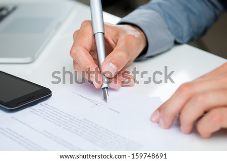 Close Up Of A Businessman Signing Legal Documents At Desk - stock photo