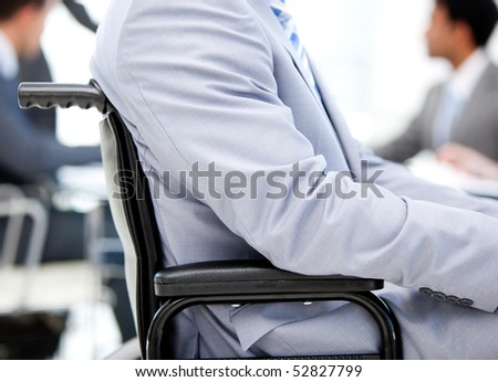 Close-up of a businessman sitting on a wheelchair in a meeting - stock photo