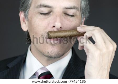 Close-up of a businessman smelling a cigar. - stock photo