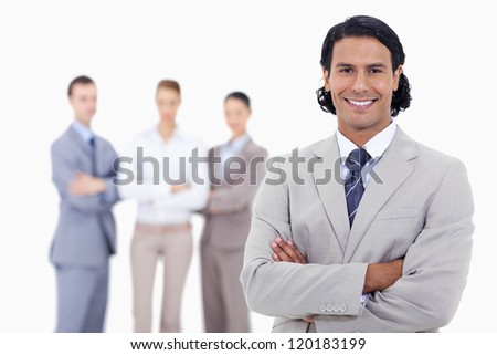 Close-up of a businessman smiling and crossing his arms with serious people in background - stock photo