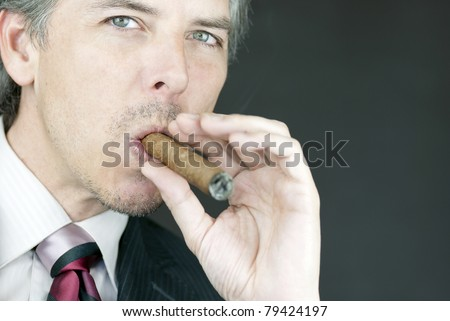 Close-up of a businessman smoking a cigar. - stock photo