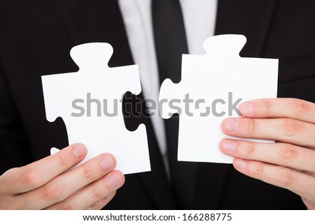 Close-up Of A Businessman Solving Jigsaw Puzzle In Office