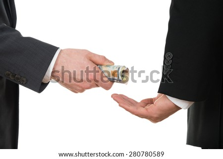 Close-up Of A Businessman Taking Bribe Over White Background