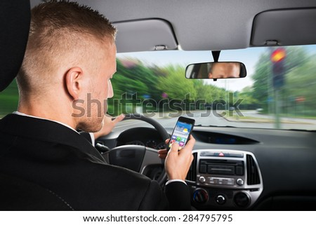 Close-up Of A Businessman Using Cellphone While Driving Car - stock photo