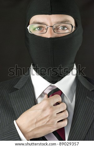 Close-up of a businessman wearing a balaclava adjusting his tie. - stock photo