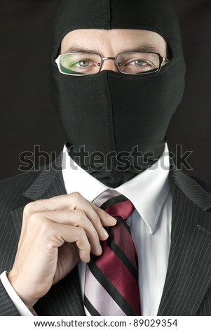 Close-up of a businessman wearing a balaclava straightening his tie. - stock photo