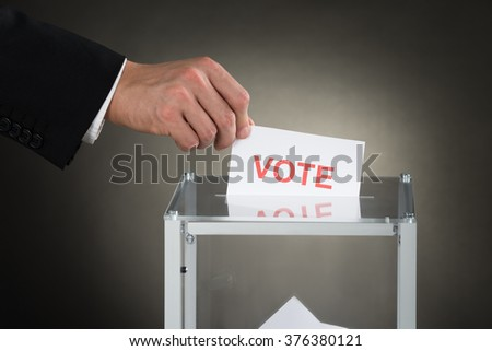 Close-up Of A Businessperson Hand Putting Vote Into Ballot Box - stock photo