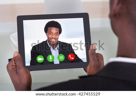Close-up Of A Businessperson Video Chatting With Colleague - stock photo