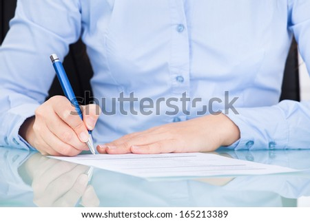 Close-up Of A Businesswoman At Desk Signing On Contract - stock photo